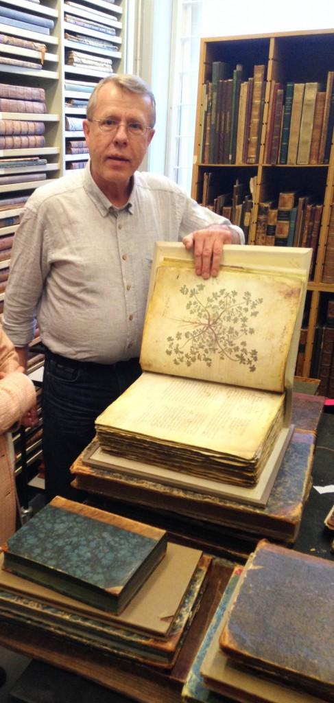 """På besøg i Botanisk Centralbibliotek – et sandt skatkammer af smukke bøger. Forfatteren til """"Fortællingen om Flora Danica"""", Henning Knudsen, viser en af de smukke tavler fra den originale Flora Danica frem."""