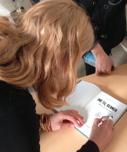 Rikke signerer Ind til kernen efter foredraget på Niels Bohr Instituttet.